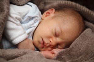 Noworodek śpi owinięty kocem